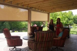 family sitting outside near Sentry patio screen